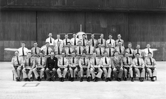 A formal group portrait of 77 Squadron RAAF pilots taken in front of one of the Squadron's new Meteor F.8 jet aircraft at Iwakuni, Japan, April 1951. This marked the commencement of their conversion from the P-51D Mustang to its replacement. Max Scannell is on front row, third from the left.