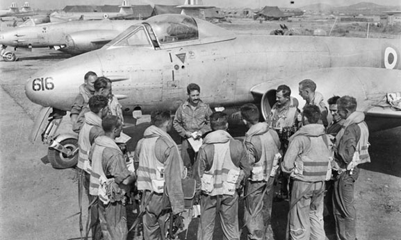 Pilots of No.77 Squadron RAAF, being briefed by their Commanding Officer, Squadron Leader Richard (Dick) Cresswell (centre, facing camera), on the Kimpo airfield tarmac in front of Meteor aircraft A77-616, prior to a mission over North Korea in 1951. Flight Lieutenant Maxwell (Max) Scannell, RAF is second from the left in the semicircle. Australian War Memorial JK0024