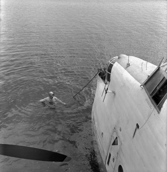 Salvage of Maritime Operational Conversion Unit Sunderland, NZ4111, after it was holed and sank in Te Whanga Lagoon, Chatham Islands. Wing Commander Henry Lionel Homer, Director of Aircraft Engineering, doing an exterior underwater inspection of the Sunderland. NB. This negative deteriorating resulting in poorer image quality.