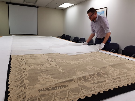 Collections Technician Jason Sim carefully preparing to put the Battle of Britain lace panel back into storage at the Air Force Museum of New Zealand.
