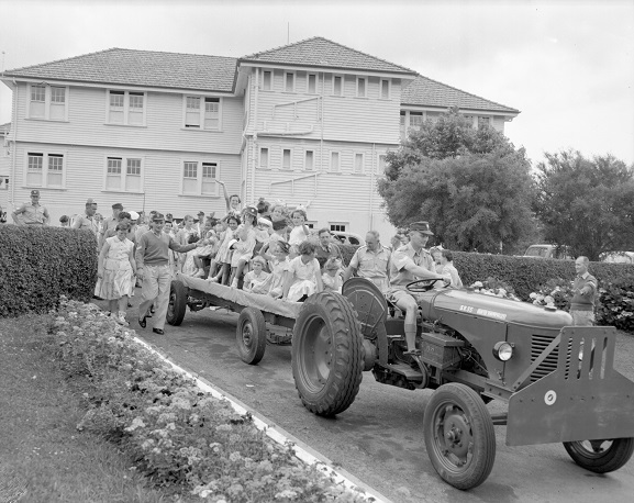 Children's Christmas parties have long been a highlight for Air Force families. Here, children are going for a ride with Santa Claus at the RNZAF Hobsonville Sergeants' Mess children's Christmas party, 1958. Image ref WhG14241-58, RNZAF Official.