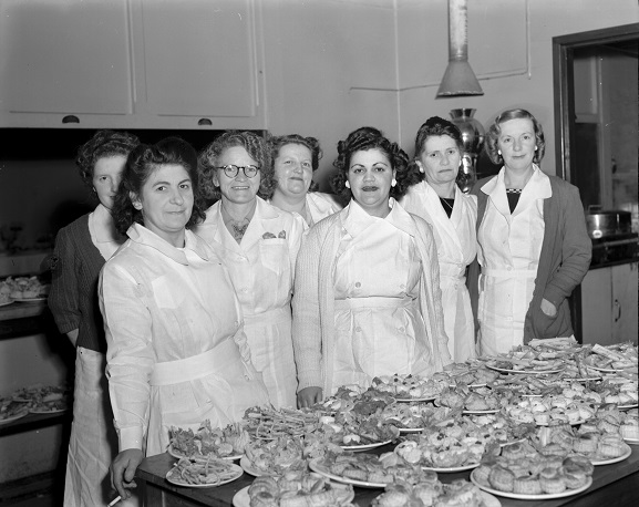 Group of catering staff with food ready for the tables at the Victory Ball.  RNZAF Station, Rongotai, September 1945. Image ref PR7393, RNZAF Official.