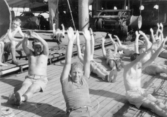 Personnel doing exercise on the deck of a ship, either 'Roggeveen' or 'Plancius', on the way to Singapore. Donald Duff (front middle). Handwritten by Donald Duff on the reverse