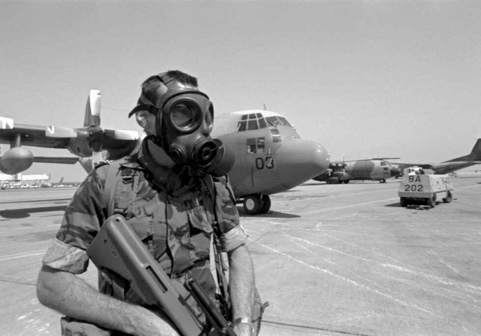 Sergeant Phil Lane, wearing a gas mask, on security duty on the tarmac in front of No. 40 Squadron Hercules NZ7003. Riyadh, Saudi Arabia, Feb-Mar 1991. Image ref PD14-2-91, RNZAF Official.
